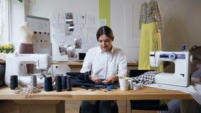 El pedazo de costura del sastre de sexo femenino joven de paño en cose el estudio almacen de metraje de vídeo