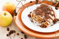 El pedazo de empanada de manzana derramado ralló el chocolate y dos manzanas frescas Imagen de archivo libre de regalías