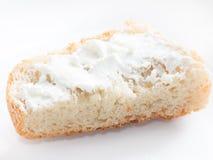 El pedazo de pan simple con requesón se separó en el aislador blanco Imagen de archivo libre de regalías
