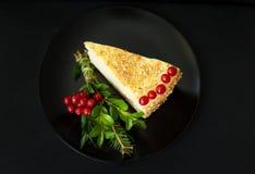 El pedazo de torta adornó el árbol de navidad y bayas rojas en una placa negra Imagen de archivo