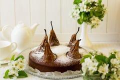 El pedazo de torta de chocolate hecha en casa con las peras adornó el flor de la pera Imagenes de archivo