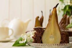 El pedazo de torta de chocolate hecha en casa con las peras adornó el flor de la pera Imagen de archivo libre de regalías
