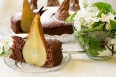 El pedazo de torta de chocolate hecha en casa con las peras adornó el flor de la pera Imágenes de archivo libres de regalías