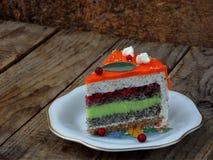 El pedazo de torta de la amapola con crema de la cal y la fresa gelatinan, cubierto con una capa de espejo Foco selectivo Imagen de archivo libre de regalías