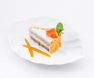 El pedazo de torta en la placa con la rosa y la menta hojea Foto de archivo libre de regalías