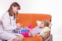 El pediatra escribe una prescripción para la niña Fotografía de archivo