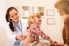 El pediatra examina a la muchacha del niño con el estetoscopio Fotografía de archivo libre de regalías