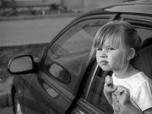 El pegarse de la niña su dirige hacia fuera la ventanilla del coche Imagen de archivo libre de regalías