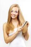 El peinarse de la muchacha de su pelo. en gris Imagenes de archivo