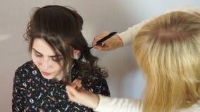 El peine del estilista separa los filamentos del pelo almacen de video