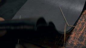 El peletero trabaja con la tela de cuero sintética Accesorio profesional hecho a mano metrajes