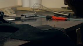 El peletero trabaja con la tela de cuero sintética Accesorio profesional hecho a mano almacen de video