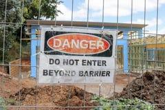 El peligro rojo, blanco y negro, hace ningún entra más allá de señal de peligro de la barrera en el emplazamiento del edificio y  Fotografía de archivo libre de regalías