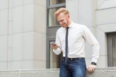El pelirrojo y el hombre de negocios barbudo tienen una videoconferencia en teléfono elegante de los hes Concepto del asunto Imagenes de archivo
