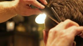 El pelo de reducción del peluquero profesional con las tijeras especiales, pelo visto vuela aparte almacen de metraje de vídeo