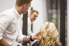 El pelo de Styling Woman del peluquero Imagen de archivo libre de regalías