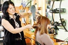 El pelo del cliente de sequía del peluquero Fotos de archivo libres de regalías