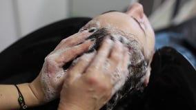 El pelo del lavado del peluquero da masajes a la cabeza almacen de video