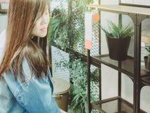 El pelo marrón largo de la muchacha asiática con mezclilla de la chaqueta azul es choos foto de archivo libre de regalías