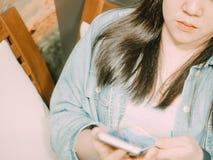 El pelo negro con la muchacha azul de la mezclilla durante uso su smartphone y se sienta Imagenes de archivo