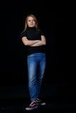 El pelo rubio deportivo de la mujer joven se está colocando con las manos dobladas Imagenes de archivo