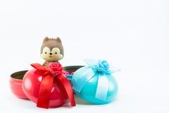 El peluche refiere la caja de regalo azul roja en el fondo blanco Fotografía de archivo libre de regalías