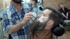 El peluquero afeita a hombres con una barba larga con la hoja de afeitar recta en salón o barbería de pelo de s Corte de pelo y e almacen de video