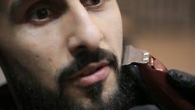 El peluquero afeita la barba del cliente con el condensador de ajuste almacen de metraje de vídeo