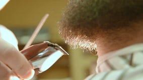 El peluquero afeita la barba del cliente con una maquinilla de afeitar eléctrica almacen de metraje de vídeo
