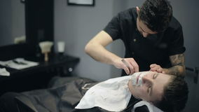 El peluquero afeita la barba del cliente en la barbería almacen de metraje de vídeo