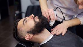 El peluquero afeita la barba del hombre que usa la maquinilla de afeitar eléctrica almacen de video