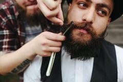 El peluquero afeita a un hombre barbudo Fotos de archivo