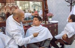 El peluquero afeita a un hombre joven en una barbería del retro-estilo durante el fin de semana Foto de archivo libre de regalías