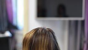 El peluquero aplica el tinte de pelo en el primer del pelo almacen de video