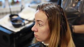 El peluquero aplica el tinte de pelo en la mujer joven del pelo en marco metrajes