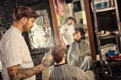 El peluquero asperja a un cliente con agua Foto de archivo libre de regalías