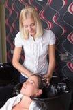 El peluquero atractivo joven lava la cabeza de la muchacha en la barbería Imagenes de archivo