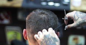 El peluquero con los tatuajes en sus manos que cortan el pelo usando cepillo para el pelo y las tijeras metrajes