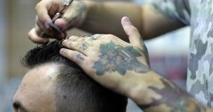 El peluquero con los tatuajes en sus manos que cortan el pelo usando cepillo para el pelo y las tijeras almacen de metraje de vídeo