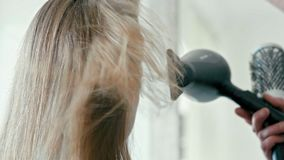 El peluquero con el secador de pelo seca el pelo femenino flutttering recto en salón metrajes