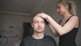 El peluquero corta al hombre del pelo en casa almacen de metraje de vídeo
