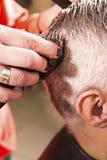 El peluquero corta el pelo Fotos de archivo