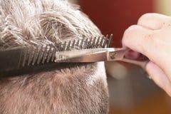 El peluquero corta el pelo Imagenes de archivo
