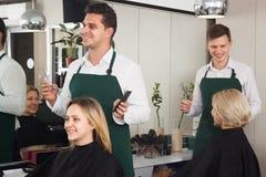 El peluquero corta el pelo de la muchacha rubia en el salón Fotografía de archivo
