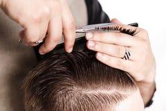 El peluquero corta el pelo del cliente satisfecho morenita en estudio Fotos de archivo