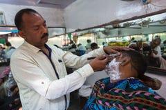 El peluquero corta el pelo del peregrino Un corte de pelo en Varanasi se considera ser una clase de ritual de la purificación en  Fotos de archivo