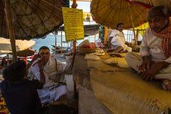 El peluquero corta el pelo del peregrino Un corte de pelo en Varanasi se considera ser una clase de ritual de la purificación en  Fotografía de archivo