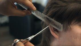 El peluquero corta el pelo en el templo y el oído al cliente en un salón Hombre que se sienta en butaca de los peluqueros mientra almacen de video
