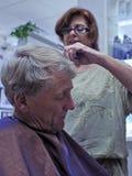 El peluquero da corte de pelo del hombre Fotografía de archivo