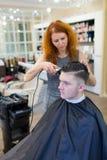 El peluquero de la muchacha con el pelo rojo rizado corta al individuo joven, hermoso en un salón de belleza Imagenes de archivo